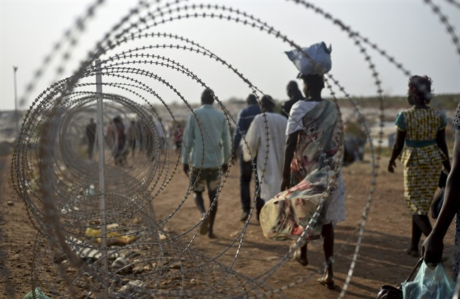 In this file photo taken Tuesday, Jan. 19, 2016, displaced people walk next to a razor wire fence at the United Nations base in the capital Juba, South Sudan.