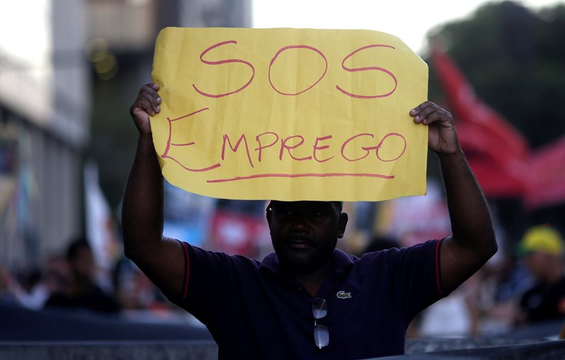 """A man holds a banner which reads """"S.O.S. employment"""" as he attends a protest on the Rio de Janeiro economic crisis, Brazil, July 6, 2016. Picture taken July 6, 2016. REUTERS/Ricardo Moraes."""