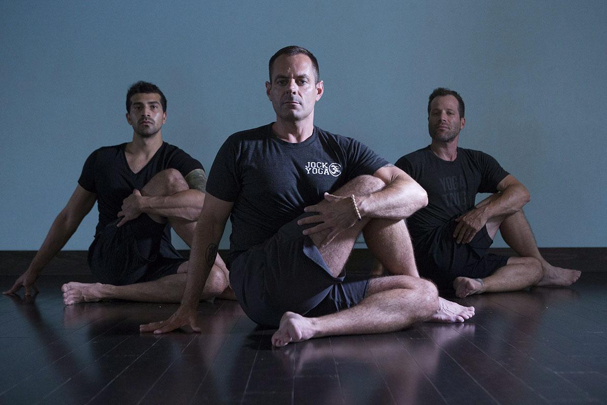 Michael DeCorte (centre) adopts a seated twist pose alongside Salmaan Sayeed (left) and Howie Track at Toronto's Moksha Yoga studio on Saturday July 9 , 2016.