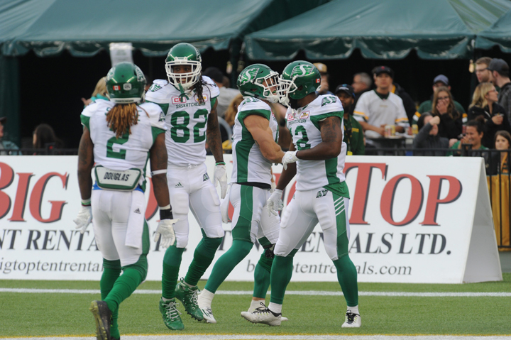 Saskatchewan Roughriders players Curtis Steele (#2), Naaman Roosevelt (#82) and John Chiles (#12) celebrate in the endzone during the 1st quarter of CFL game action between the Edmonton Eskimos and the Saskatchewan Roughriders on Friday, July 08, 2016.
