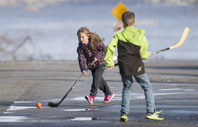Emile Castonguay and his sister Adele, left, play a game of ball hockey in Vaudreuil-Dorion, west of Montreal, on Dec. 24, 2015.