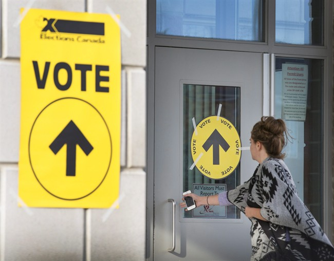 A woman enters Maple High School in Vaughan, Ont., to cast her vote in the Canadian federal election on Monday, Oct. 19, 2015.