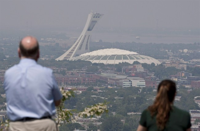"""Tourists look through out through smog at Montreal's Olympic Stadium in a May 31, 2010, file photo. It's been dubbed the """"Big Owe"""" for its runaway construction costs and it has attracted widespread derision for falling concrete and roof rips but Montreal's Olympic Stadium doesn't just have detractors."""