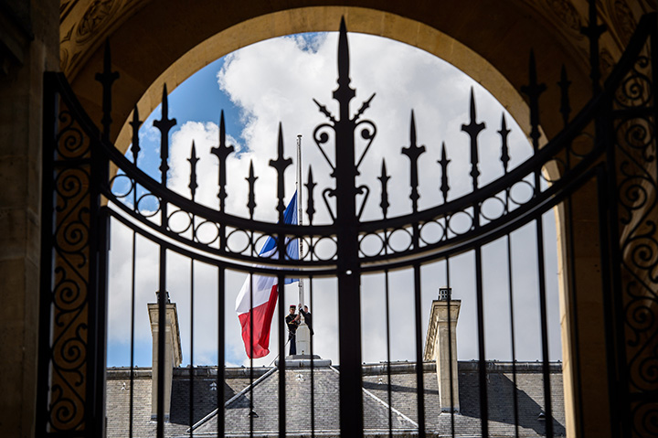 A picture taken through the gate shows French Republican guards placing the French flag at half-staff at the Elysee presidential Palace, in Paris, on July 15, 2016.