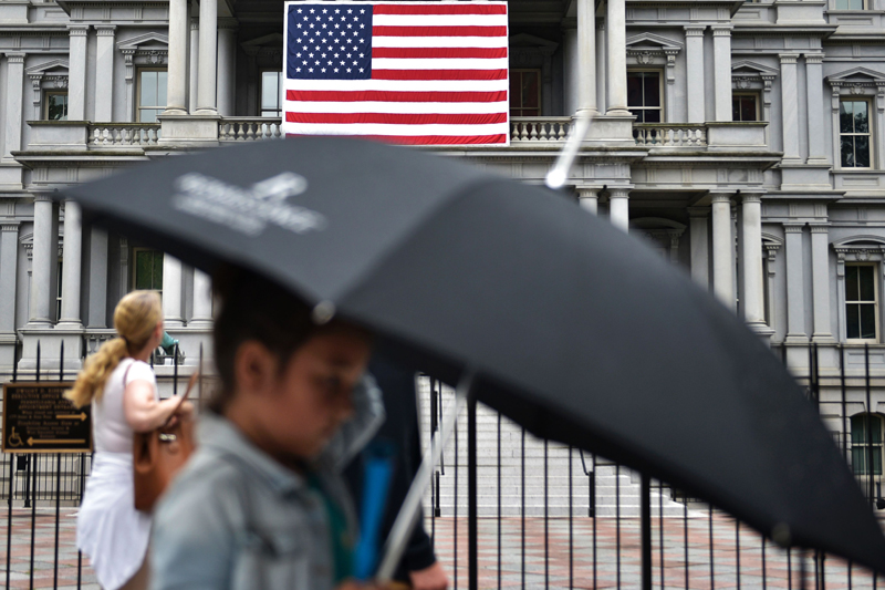 A boy carries an umbrella while walking in front of the Eisenhower Executive Office Building, next to the White House, on Independence Day, in Washington, DC on July 4, 2016.