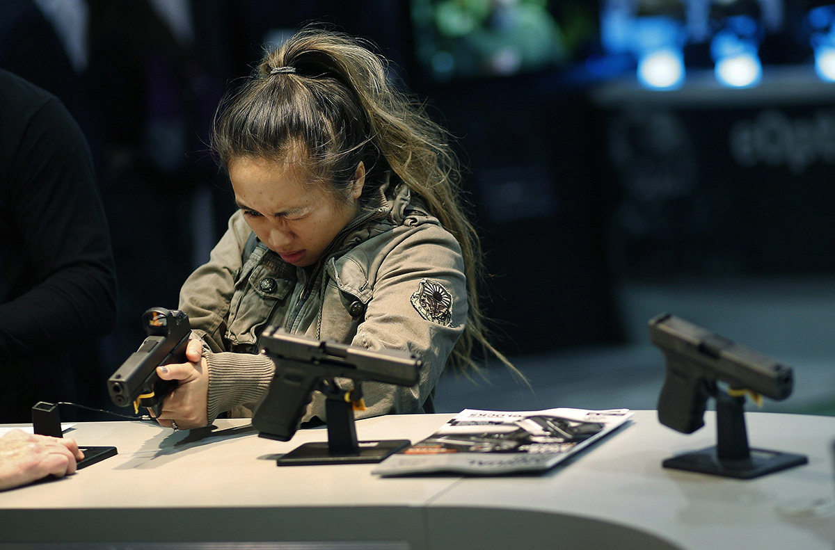 In this Jan. 19, 2016 file photo, a woman looks at a handgun at the Glock booth at the Shooting Hunting and Outdoor Trade Show in Las Vegas.