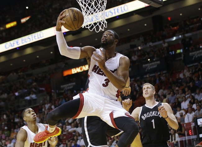 Miami Heat guard Dwyane Wade (3) shoots in front of Brooklyn Nets center Mason Plumlee (1) during the first half of an NBA basketball game in Miami.