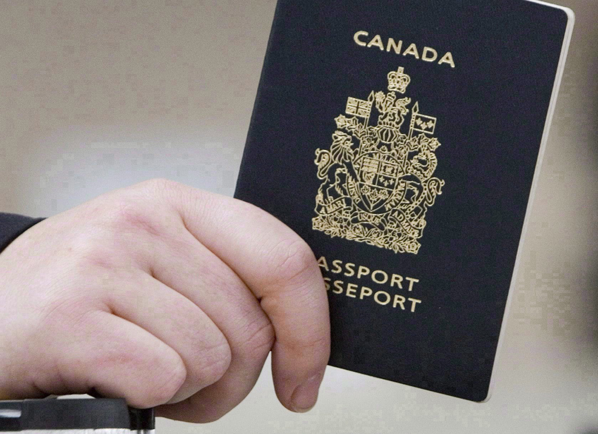 A passenger holds a Canadian passport before boarding a flight in Ottawa on Jan 23, 2007. Federal officials used photo-matching technology to identify 15 high-risk people - all wanted on immigration warrants - who used false identities to apply for travel documents.
