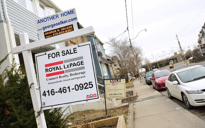 Real estates 'For Sale' signs displayed in front of homes on Woodbine Ave in Toronto on March 12, 2016.