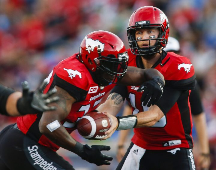 Calgary Stampeders' quarterback Bo Levi Mitchell, right, hands the ball off to Jerome Messam during first half CFL football action against the Saskatchewan Roughriders in Calgary, Thursday, Aug. 4, 2016.