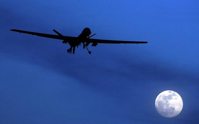 An unmanned U.S. Predator drone flies over Kandahar Air Field, southern Afghanistan, on a moonlit night.