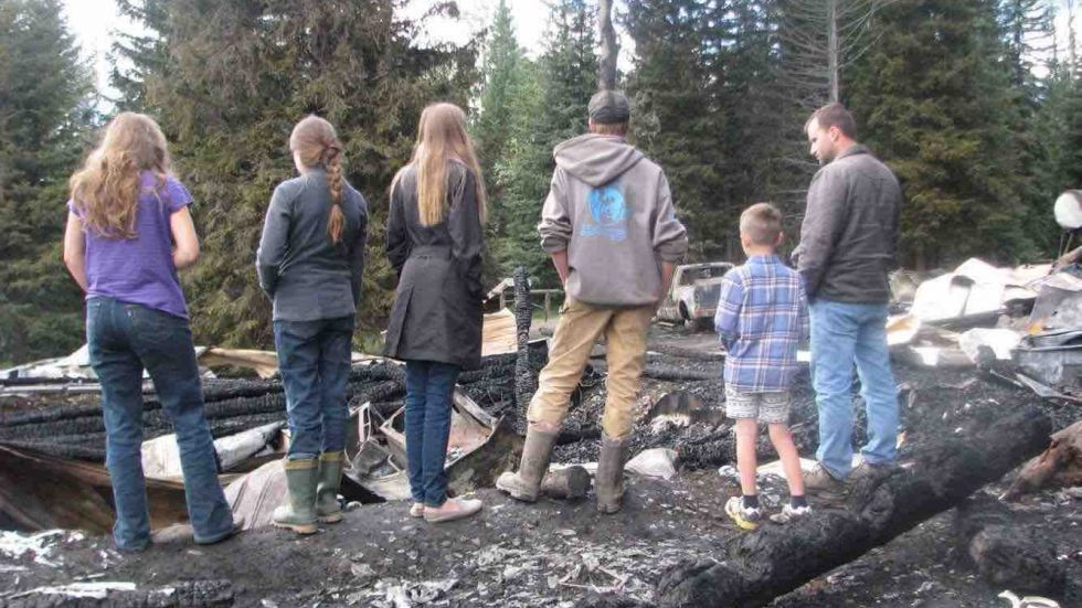 The Duits family surveys the wreckage of their family home after a fire at their home near 100 Mile House.