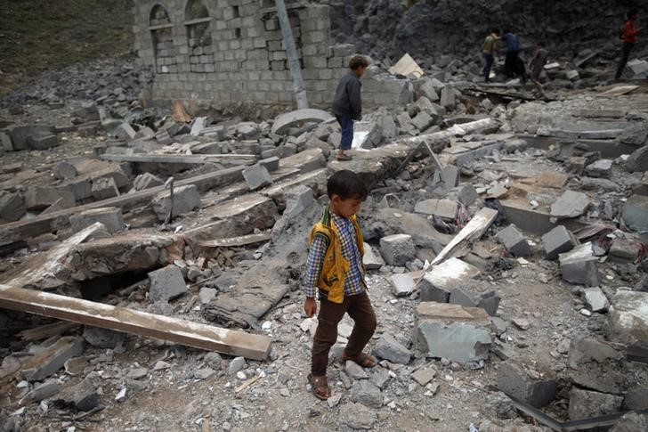 A boy walks on rubble of a house after it was destroyed by a Saudi-led air strike in Yemen's capital Sanaa, August 11, 2016.