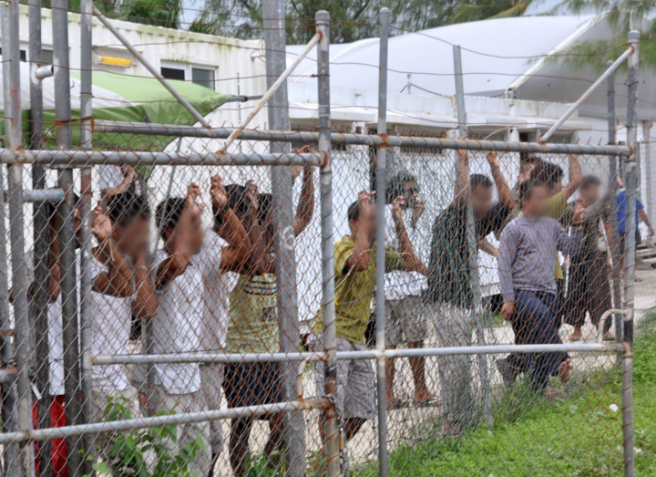 Asylum seekers look at the media from behind a fence at the Manus Island detention centre, Papua New Guinea in this picture taken March 21, 2014.