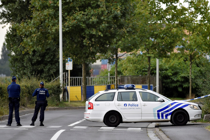 Belgian police officers secure a road near the Belgium's National Institute of Criminology after arsonists set fire to it in Brussels, Belgium August 29, 2016.