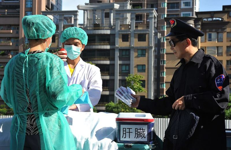 Members of the spiritual movement Falungong act out a scene of stealing human organs to sell during a demonstration in Taipei on July 20, 2014 against China's persecution of the group. China outlawed Falungong as an 'evil cult' in 1999 and has since detained tens of thousands of members. AFP PHOTO / Mandy CHENG.