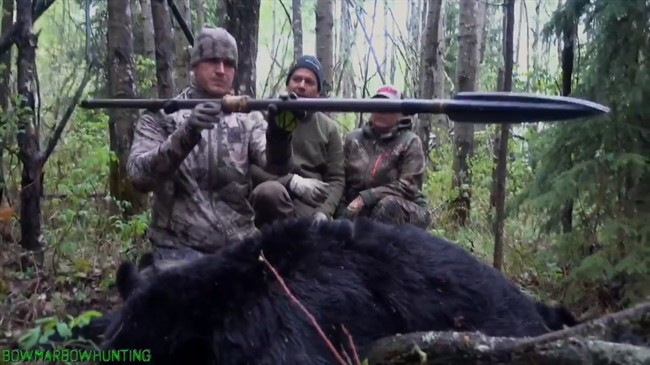 American Josh Bowmar, seen here at left in a still image made from video, displays the spear with which he killed a large black bear, which resulted in a public backlash in 2016.