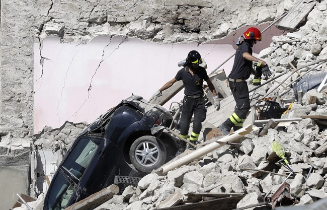 Rescuers make their way through destroyed houses following an earthquake in Italy, in August 2016. Some scientist believe climate change is triggering more earthquakes.