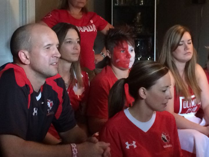 Jen Kish's fiancee Nadene Selewich (second from the left) and best friend Jay Keddie-Thomson (second from the right) watch the women's rugby sevens bronze medal game.