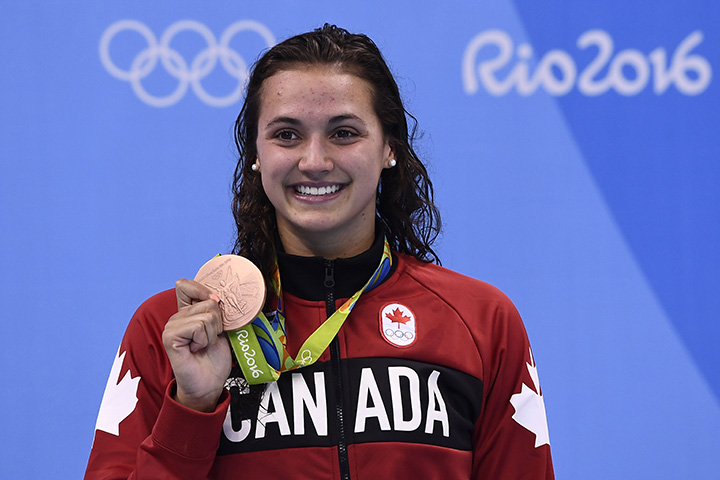 Canada's Kylie Masse poses with her bronze medal on the podium of the Women's 100m Backstroke during the swimming event at the Rio 2016 Olympic Games at the Olympic Aquatics Stadium in Rio de Janeiro on August 8, 2016.