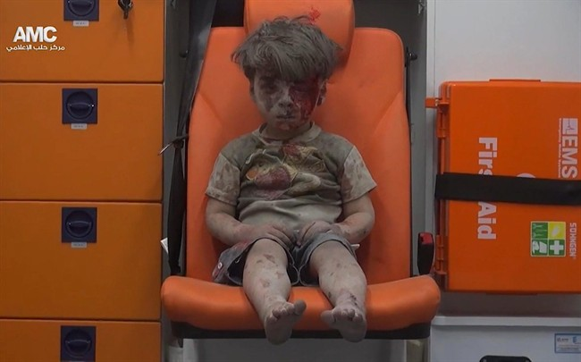 In this frame grab taken from video provided by the Syrian anti-government activist group Aleppo Media Center (AMC), a child sits in an ambulance after being pulled out or a building hit by an airstirke, in Aleppo, Syria, Wednesday, Aug. 17, 2016. Syrian opposition activists reported an airstrikes on the al-Qaterji neighborhood in Aleppo late Wednesday. (Aleppo Media Center via AP).