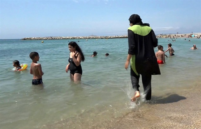 FILE - In this Aug.4 2016 file photo made from video, Nissrine Samali, 20, gets into the sea wearing traditional Islamic dress, in Marseille, southern France. The French resort of Cannes has banned full-body, head-covering swimsuits worn by some Muslim women from its beaches, citing security concerns. A City Hall official said the ordinance, in effect for August, could apply to burkini-style swimsuits. (AP Photo, File).