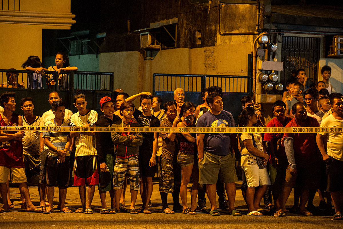 In this photo taken on July 19, 2016, shows residents behind a police line looking at the two dead bodies of an alleged drug dealer after a drug bust operation that turned into a gun fight in Manila.