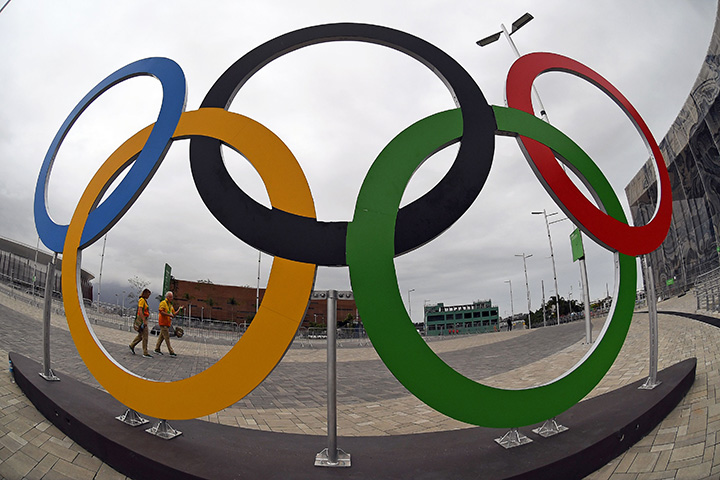 Volunteers walk past a set of Olympics Rings at the Olympics Park in Rio de Janeiro on August 3, 2016 ahead of the Olympic Games.