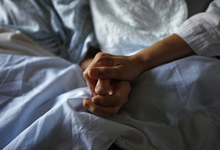 A woman holds the hand of her mother who is dying from cancer during her final hours at a palliative care hospital in Winnipeg in this image from 2010.