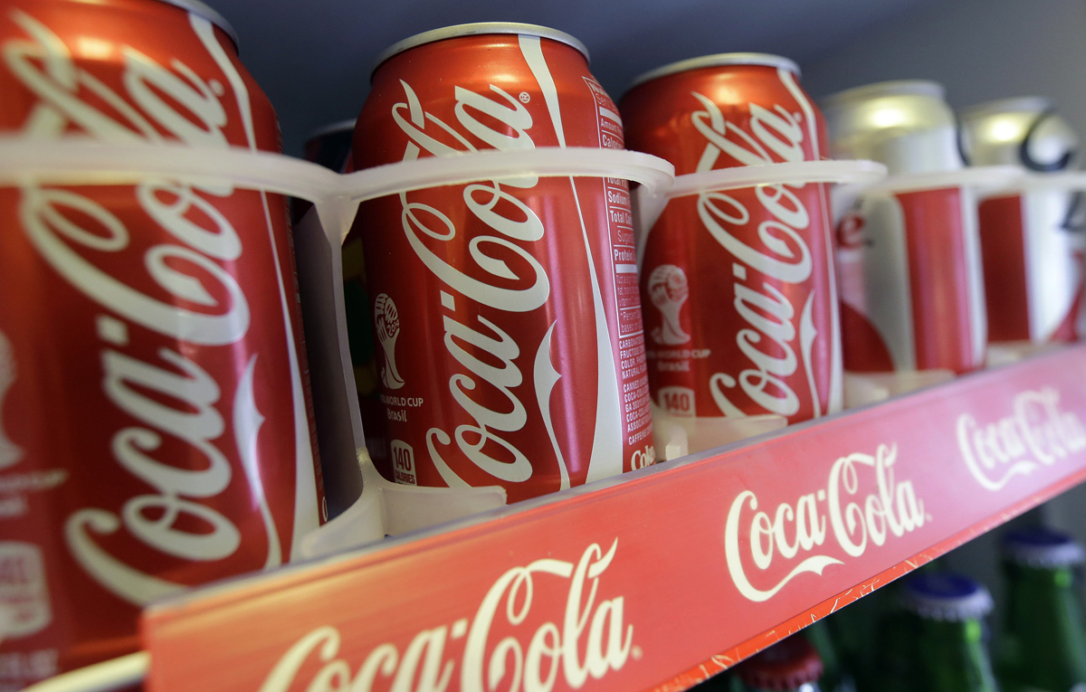 In this June 30, 2014 photo cans of Coca-Cola soda pop are shown in the refrigerator inside of Chile Lindo in San Francisco. San Francisco and Berkeley are aiming to become the first U.S. cities to pass per-ounce taxes on sugary drinks.