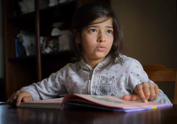 Syrian refugee Rim Younis, 12, practices her English reading skills at her home in Calgary, Alta., .
