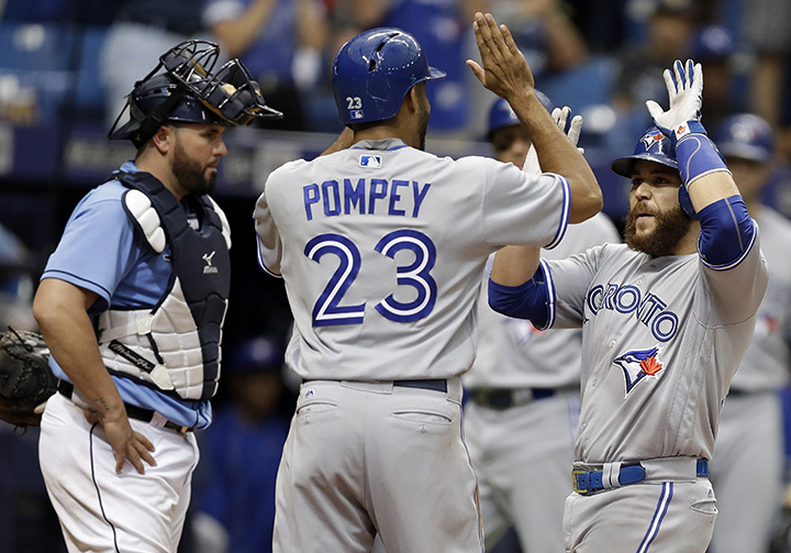 Toronto Blue Jays' Russell Martin, right, celebrates with Dalton Pompey after hitting a two-run home run off Tampa Bay Rays relief pitcher Kevin Jepsen during the eighth inning of a baseball game Sunday in St. Petersburg, Fla. Rays catcher Bobby Wilson, left, looks on.