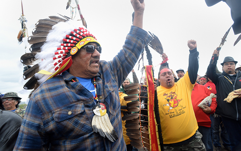 JR American Horse, left, raises his fist with others while leading a march to the Dakota Access Pipeline site in southern Morton County North Dakota. Several hundred protesters marched about a mile up Hwy 1806, Friday Sept. 9, 2016, from the protest camp to the area of the pipeline site where some archeological artifacts have been discovered.