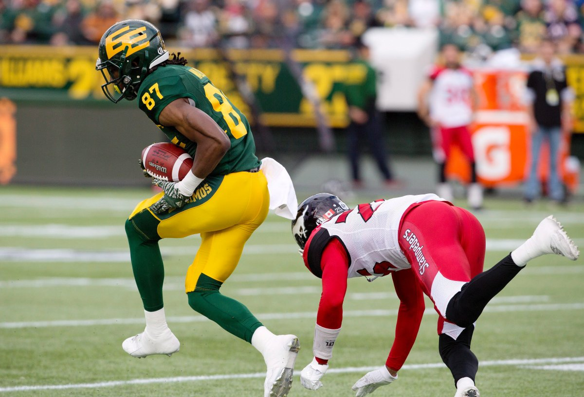 Calgary Stampeders Tommie Campbell (25) tries to stop Edmonton Eskimos Derel Walker (87) as he makes the interception for a touchdown during first half CFL action in Edmonton, Alta., on Saturday September 10, 2016.