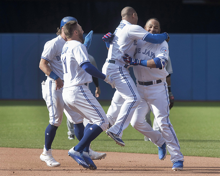 Toronto Blue Jays Edwin Encarnacion (right) is mobbed by teammates (left to right) Josh Donaldson, Kevin Pillar and Ezequiel Carrera after he drove in the winning run in the ninth inning of their American League MLB baseball game against the New York Yankees in Toronto Sunday.