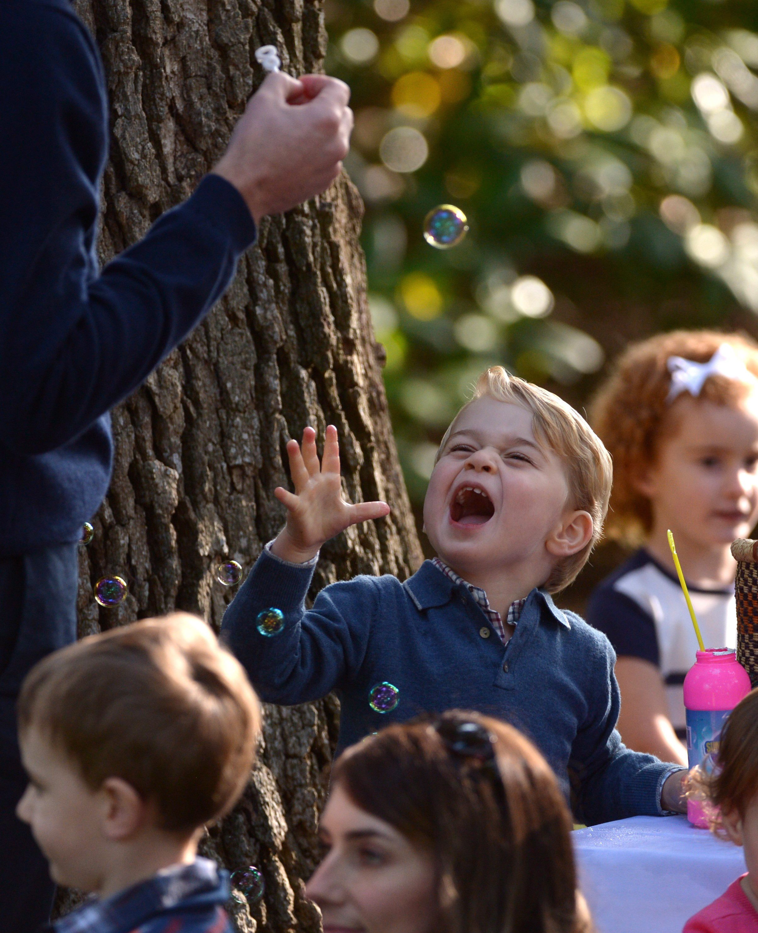 Prince George plays with bubbles during a children's tea party at Government House in Victoria, Thursday, Sept. 29, 2016. THE CANADIAN PRESS/Jonathan Hayward