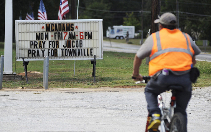 A bicyclist rides past a sign urging prayer for victims of a school shooting in Townville, S.C., on Thursday, Sept. 29, 2016.