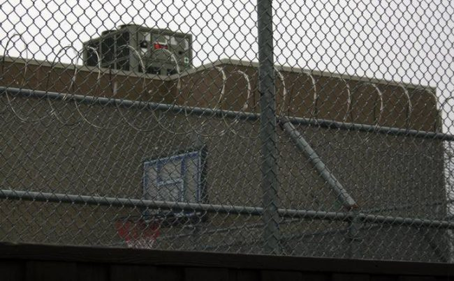 A basketball net can be glimpsed behind razor wire at the Toronto Immigration Holding Centre.