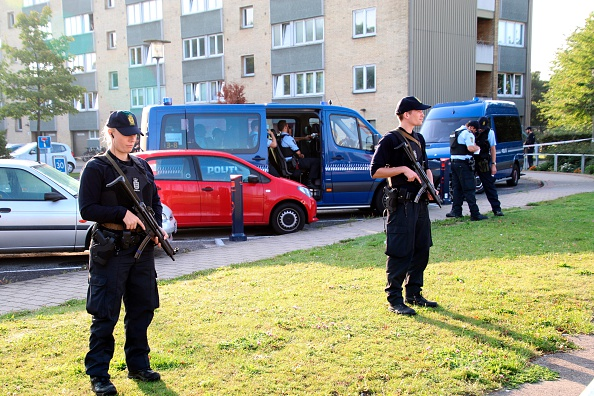 Policemen guard the area where a shooting took place in at Copenhagen's Christiania district, on September 1, 2016.  Two police officers were wounded in a shootout during an arrest of a suspected person.