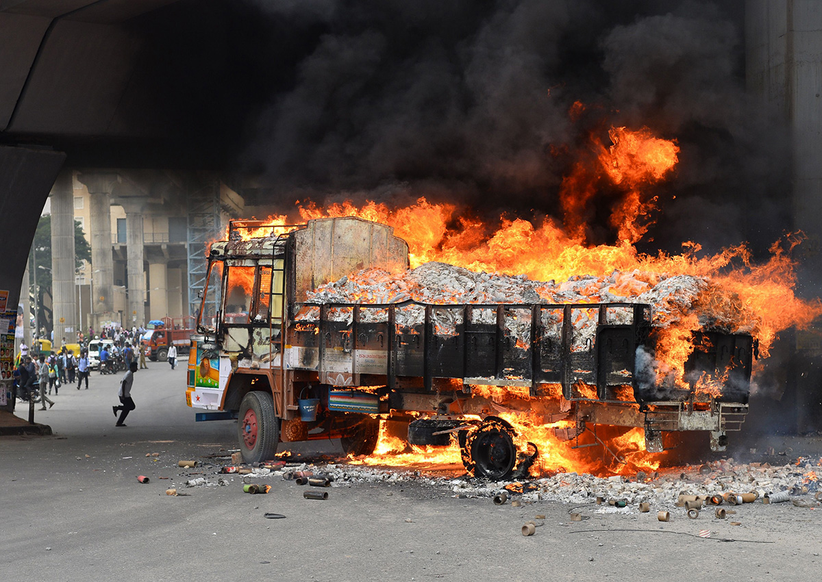 A truck from neighbouring state Tamil Nadu burns after it was set alight by agitated pro-Karnataka activists as the Cauvery water dispute erupted following the Supreme Court's order to release water to Tamil Nadu, in Bangalore on September 12, 2016.   Cauvery water agitation in Karnataka has been increasing ever since the recent Supreme Court order to the state to release 15,000 cusecs of Cauvery water a day to neighbouring state, Tamil Nadu. Karnataka is facing an acute shortage of water in its reservoirs and rivers as the state has only received subpar rainfall in the catchment areas leading to protests by farmers and pro Kannada organisations refusing to share water with its neighbouring state. / AFP / MANJUNATH KIRAN        (Photo credit should read MANJUNATH KIRAN/AFP/Getty Images).