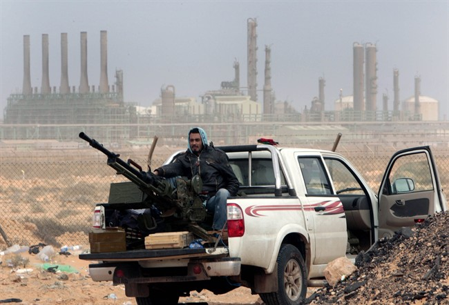 In this March 2011 file photo, an anti-government rebel sits with an anti-aircraft weapon in front an oil refinery in Ras Lanouf, eastern Libya.