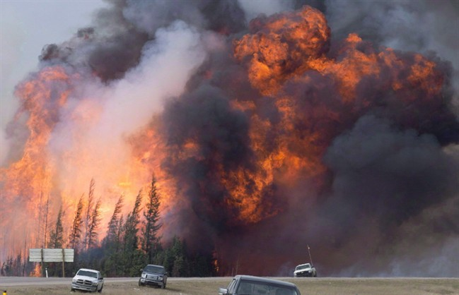A giant fireball is visible as a wildfire rips through the forest by Highway 63, 16 kilometres south of Fort McMurray, Alta on Saturday, May 7, 2016.