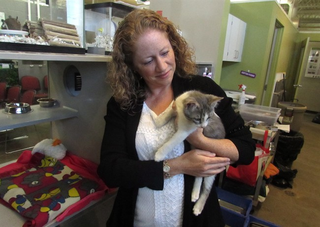 Sage Pullen McIntosh from the Calgary Humane Society poses with one of the adoptees at the shelter on Tuesday Sept. 13, 2016.
