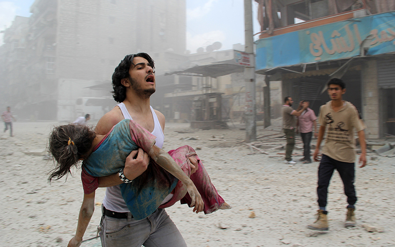 A man carries a young girl who was injured in a reported barrel-bomb attack by government forces in the northern city of Aleppo.