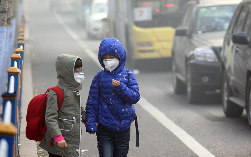 Two children wearing face masks walk in heavy smog on November 3, 2015 in Harbin, Heilongjiang Province of China.