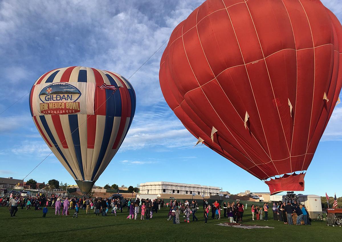 Two hot air balloons inflate at Vista Grande Elementary School in Rio Rancho, N.M. on Friday, Sept. 30, 2016, as part of the Albuquerque Aloft program that lifts balloons on school grounds as part of the 45th Albuquerque International Balloon Fiesta.
