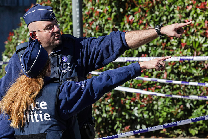 Police investigate the scene where a man stabbed two police officers, in the Schaerbeek neighbourhood in Brussels, Wednesday, Oct. 5, 2016.