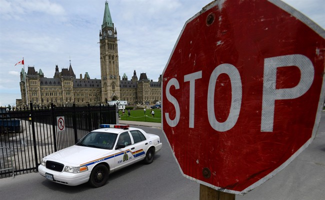 An RCMP cruiser drives past a stop sign on Parliament Hill in Ottawa on Thursday, June 13, 2013.