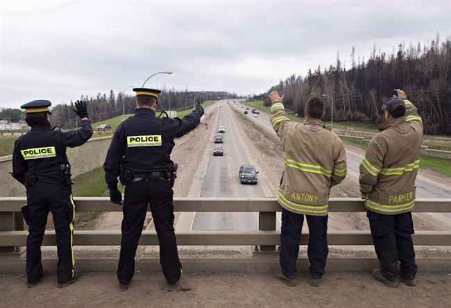 Firefighters and police welcome people into Fort McMurray Alta, on Wednesday June 1, 2016.
