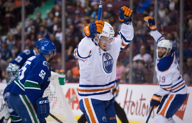 Edmonton Oilers' Drake Caggiula, centre, and Patrick Maroon, back right, celebrate Caggiula's goal against Vancouver Canucks' goalie Ryan Miller, back left, during the first period of a pre-season NHL hockey game in Vancouver, B.C., on Wednesday September 28, 2016.